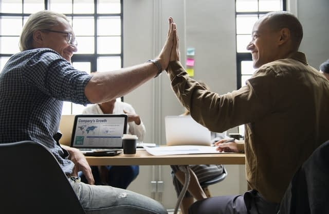Two employees giving each other a high five.