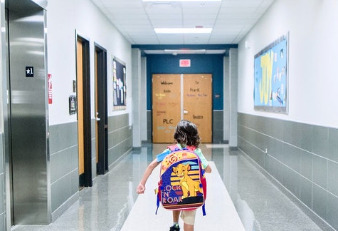 Student wearing a backpack running down a school hallway